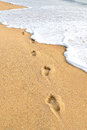 Footprints on beach the with a wave in sunset Royalty Free Stock Photo