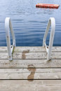 Footprints on dock at summer lake wet with ladder and diving platform calm in ontario canada Stock Image