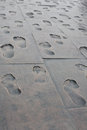 Footprints of people on the metal slabs different in footpath Royalty Free Stock Photo