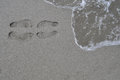 Footprints in the sand on sandy beach and sea Stock Images