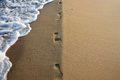 Footprints in the sand with sea wave and natural straight coast line Royalty Free Stock Photo