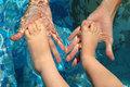 Foots of the child in palms of mother Stock Photos
