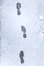 Footsteps on a snowy asphalt viewed from above Royalty Free Stock Images