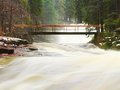Force of Nature. Huge stream of rushing water masses below small footbridge. High cascade in forest.