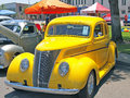 Ford coupe this is a nicely restored bright yellow with chrome wheels and minimal striping accents Stock Photo