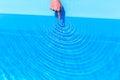 Forefinger making waves as circles in swimming pool