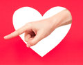 Forefinger of woman something shows against red heart Stock Photography