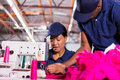 Foreman helping machinist textile factory young sewing in clothing factory Royalty Free Stock Photos