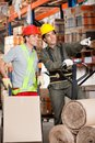 Foreman showing something to coworker at warehouse with fork pallet truck Royalty Free Stock Photo