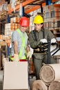 Foreman showing something to coworker at warehouse with handtruck Stock Image