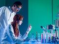 Forensic scientists studying a cartridge side view of two caucasian looking at red with fingerprints on in laboratory Royalty Free Stock Photography