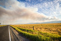Forest fire over wheat field and highway Royalty Free Stock Photo