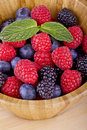 Forest fruits berries blueberries strawberries blackberries in wooden container Royalty Free Stock Images