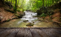Forest waterfall and rocks covered with moss and wood pier Royalty Free Stock Images