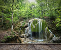 Forest waterfall and rocks covered with moss and wood pier Stock Image