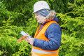 Forest worker with withered branch and tablet PC Royalty Free Stock Photo