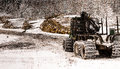 Forestry tracktor parked in front of stacks with lumber in winter landscape Royalty Free Stock Photos