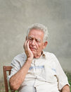 Forgetful old man elderly in thought with hand on his cheek Royalty Free Stock Image
