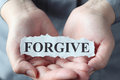 Forgive torn piece of paper with the word in the woman s palms Royalty Free Stock Photos
