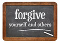 Forgive yourself and others advice white chalk text n on a vintage slate blackboard Stock Images