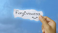 Forgiveness created hand holding a note Royalty Free Stock Photo