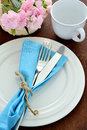 Fork and knife with dish, cup, flower on wooden table. Royalty Free Stock Photo