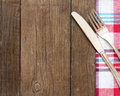 Fork and knife on kitchen towel and old wooden table Royalty Free Stock Photo