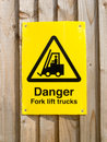 Fork lift sign danger trucks attached to fencing Royalty Free Stock Photo