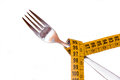 Fork with tape measure seen up close on a white background Royalty Free Stock Photography