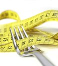 Fork wrapped in measure tape in diet and overweight concept close up Stock Images