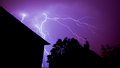 Forked lightning strike from thunder storm over house roof Stock Photo