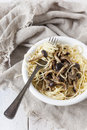 Forkful of italian pasta spaghetti with fresh pioppini mushrooms on plate white table napkin Stock Image