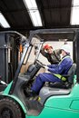 Forklift driver communicating with colleague at warehouse Stock Photos