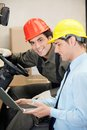 Forklift driver with supervisor using laptop portrait of young at warehouse Stock Images