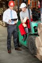 Forklift driver and supervisor at warehouse working in Stock Image