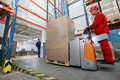 Forklift loader with cardboard freight moving in storehouse another worker watching him Stock Photo