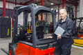 Forklift mechanic with manual proud posing next to a refurbished the in his hand Stock Photo