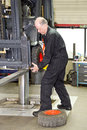 Forklift mechanic at work replacing a front tyre on a in a workshop Stock Images