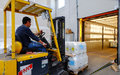 Forklift in motion at warehouse operator lifting liquid containers the industrial district of rome Stock Photo