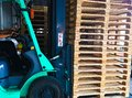 stock image of  Forklift operator handling wooden pallets in warehouse cargo for transportation to customer factory