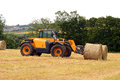 Forklift telehandler with straw bales in field yellow taking a break from loading a farmers Royalty Free Stock Photos