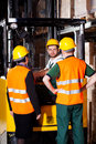 Forklift worker with management pair of managers talking young at warehouse Stock Image