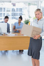 Forlorn businesswoman leaving office after being let go carrying box of things Stock Images