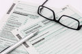 Form of income tax return with pen and glasses Royalty Free Stock Photo