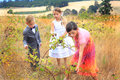 Formal children eating blackberries three a little boy in a suit and two little girls in nice dresses in a field of tall grass Stock Image