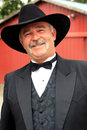 Formal cowboy portrait a happy middle aged american rancher with a full mustache wearing western wear with barn in background Royalty Free Stock Photo