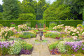 Formal english garden landscaped flagged with summer flowers and a stone vase Stock Photos