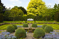 Formal english garden large with topiary shrubs and stone ornament by the pond Stock Photo