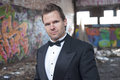 Formal style in ghetto well dressed handsome caucasian man wearing tuxedo trashy urban setting Stock Photography