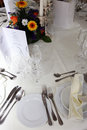 Formal table setting high angle view of a at wedding reception or catered event with white linen silverware glassware a menu and Stock Photography